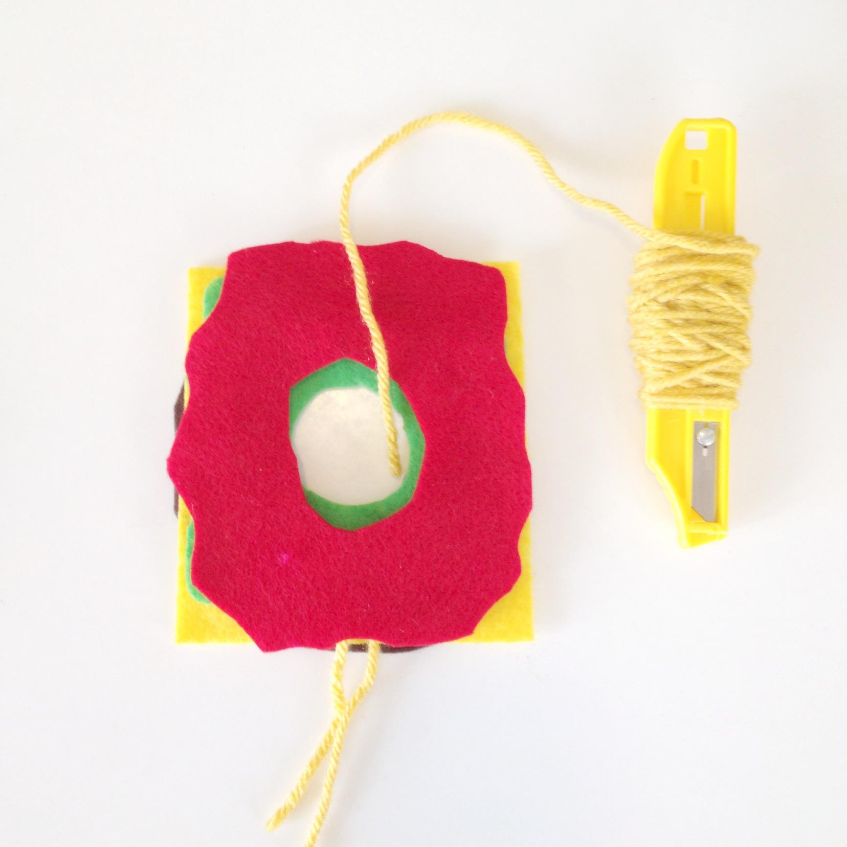 make a spool to save time   Make a Yarn Spool   How to Make a Pom Pom with Yarn   DIY Pom Pom Burger from the Pop Shop America Blog