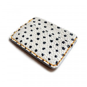 side angle of black and white polka dot leather wallet