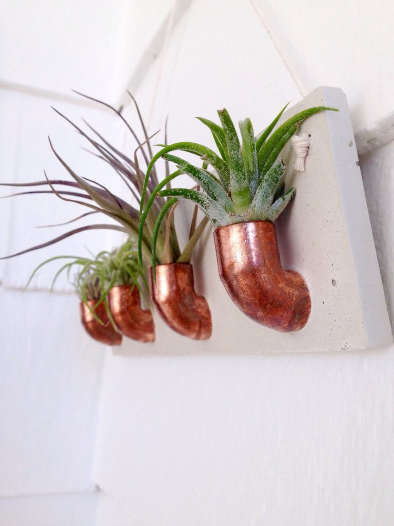 side view of large copper concrete wall hanging planter