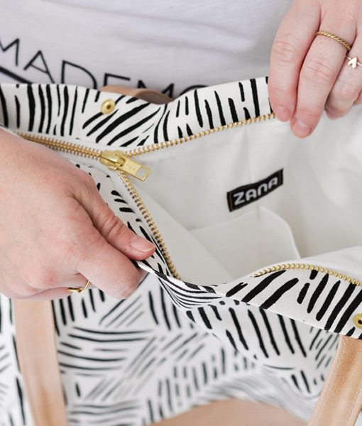 zipper closure on striped canvas and leather tote purse