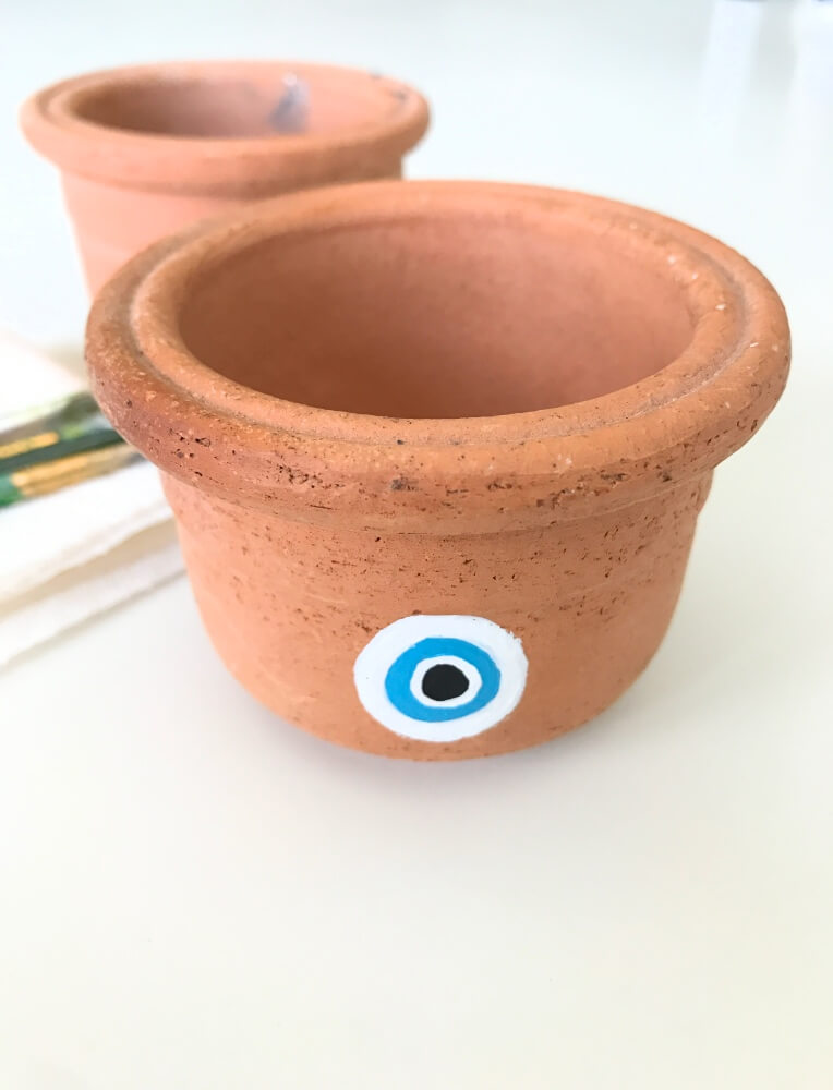 adding more white paint hand painted evil eye pot pop shop america