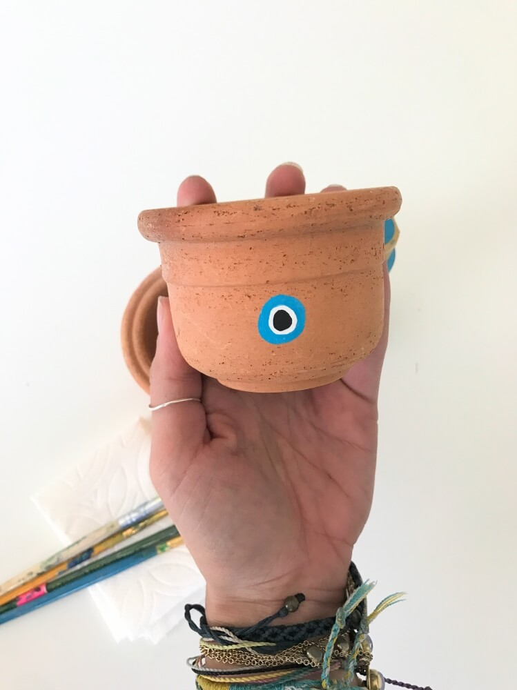 make alternating rings of blue white and black paint - how to make an evil eye planter