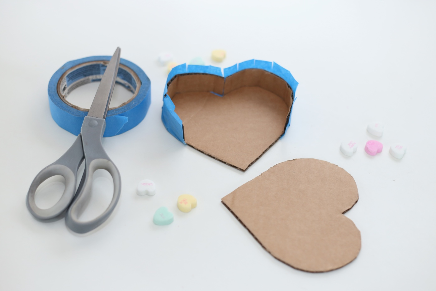 taping the cardboard pieces together diy heart pinata pop shop america
