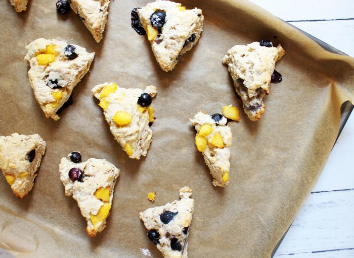 baked peach blueberry scones on baking sheet