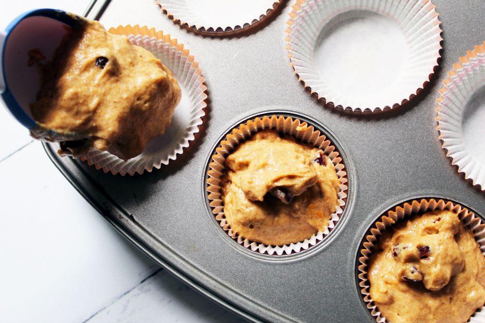 spoon pumpkin cranberry walnut batter into muffin tin
