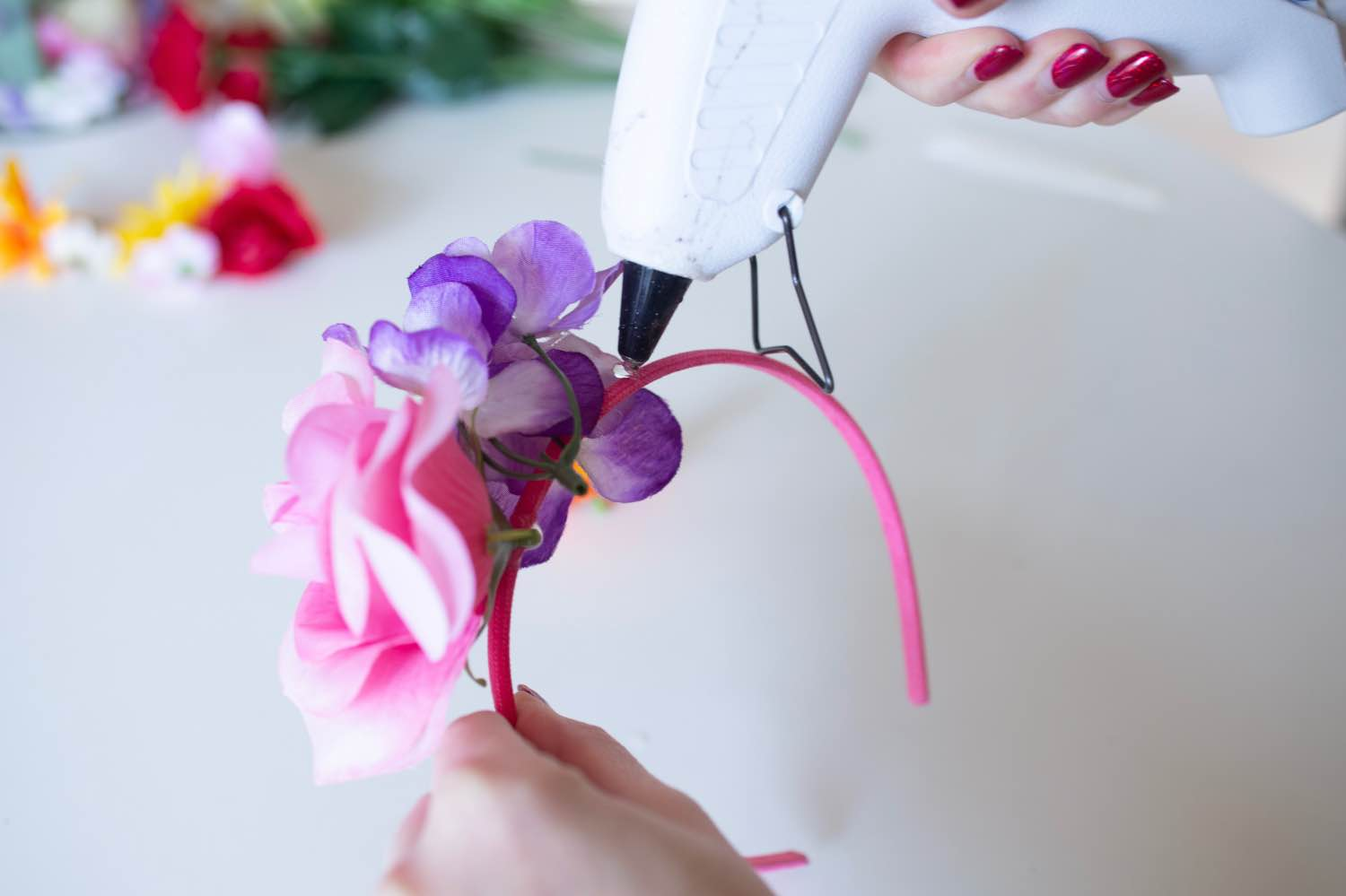 add more faux flowers to the headband with hot glue - diy flower crown pop shop america