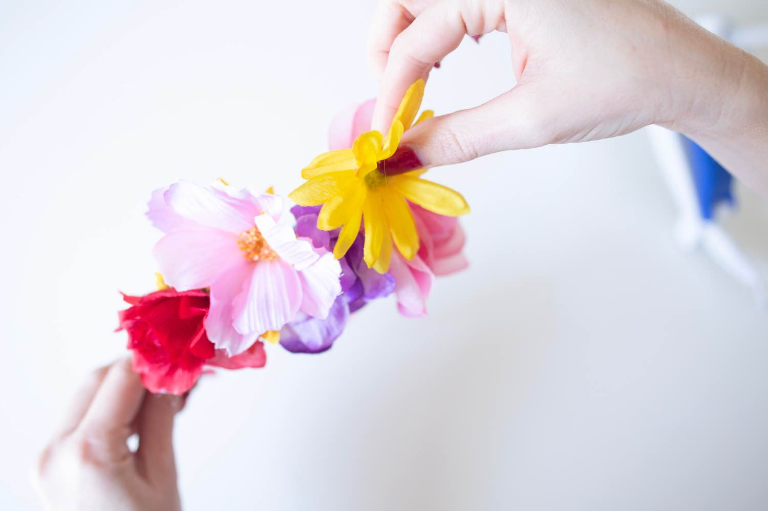 adding large and small flowers to make a diy flower crown