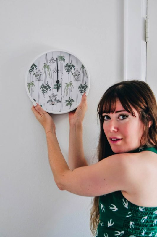 brittany bly holding up a society6 clock