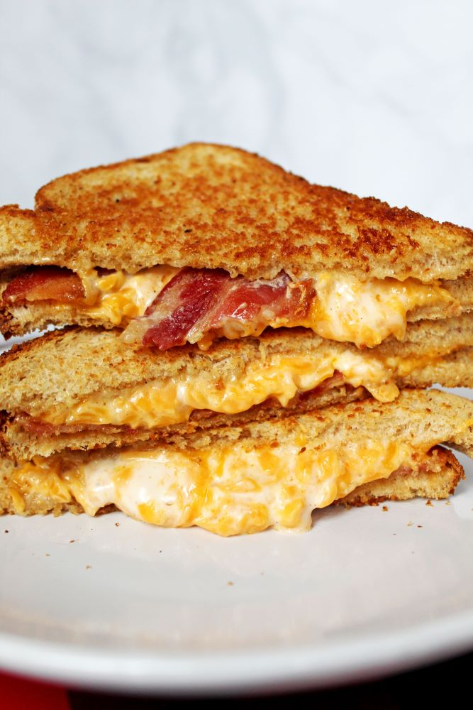 3 stack on plate of bacon cheddar ranch grilled cheese 1