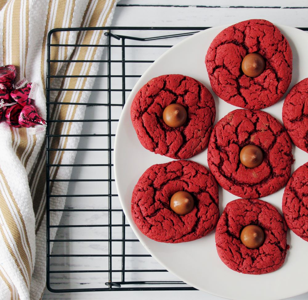red velvet cherry kiss cookies on plate on cooling rack 1