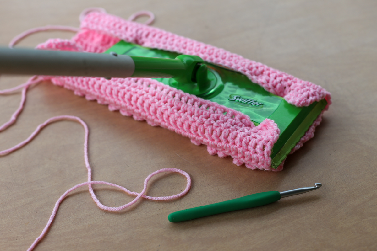 angled view of crocheted swiffer pad and swiffer and yarn