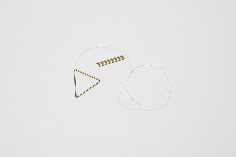 stringing together copper pipe to make a himmeli sculpture