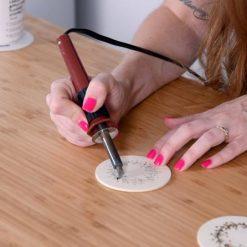 hand using wood burning tool on wood coasters