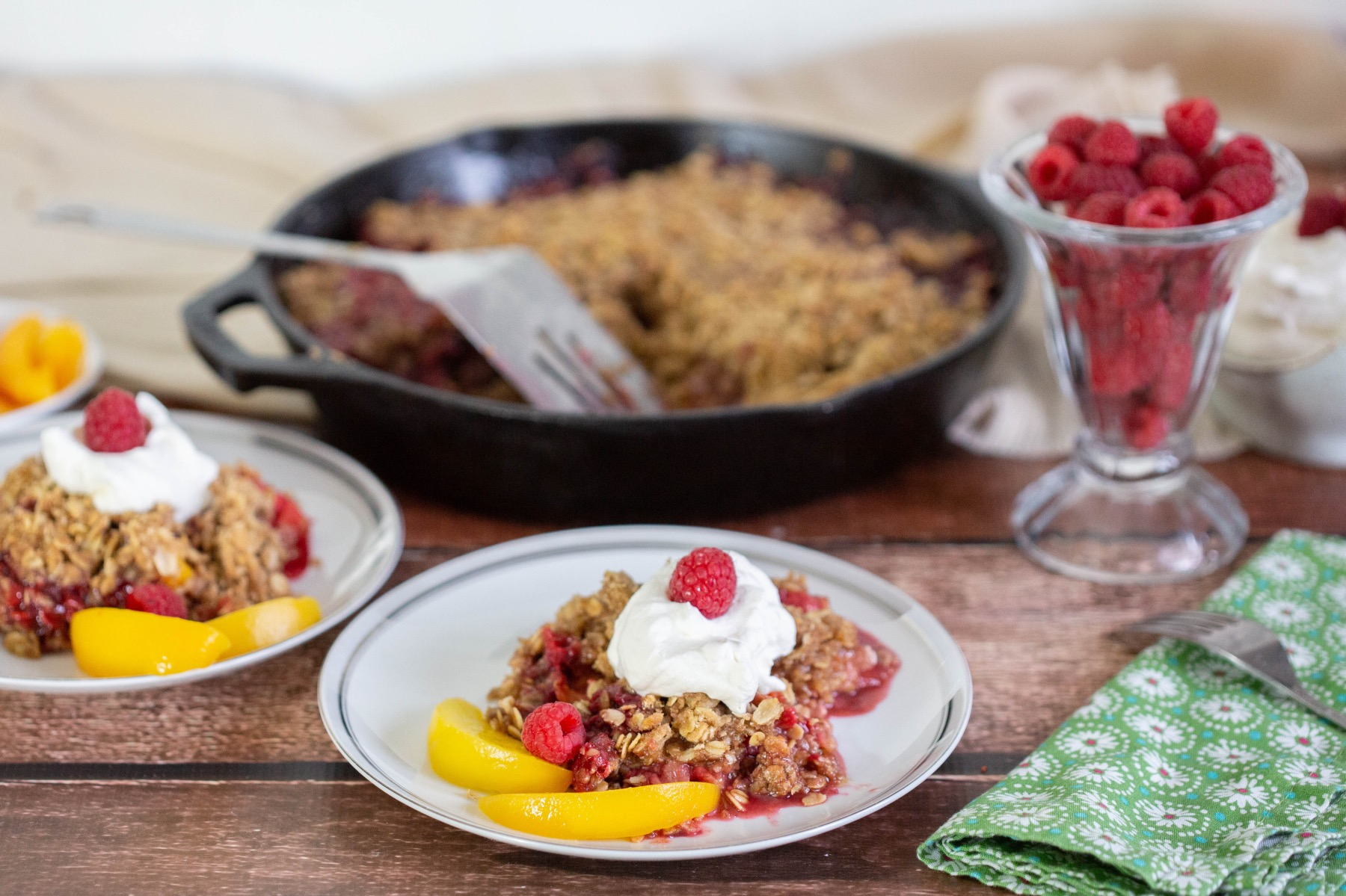 serve the peach crumble with whipped cream and raspberries