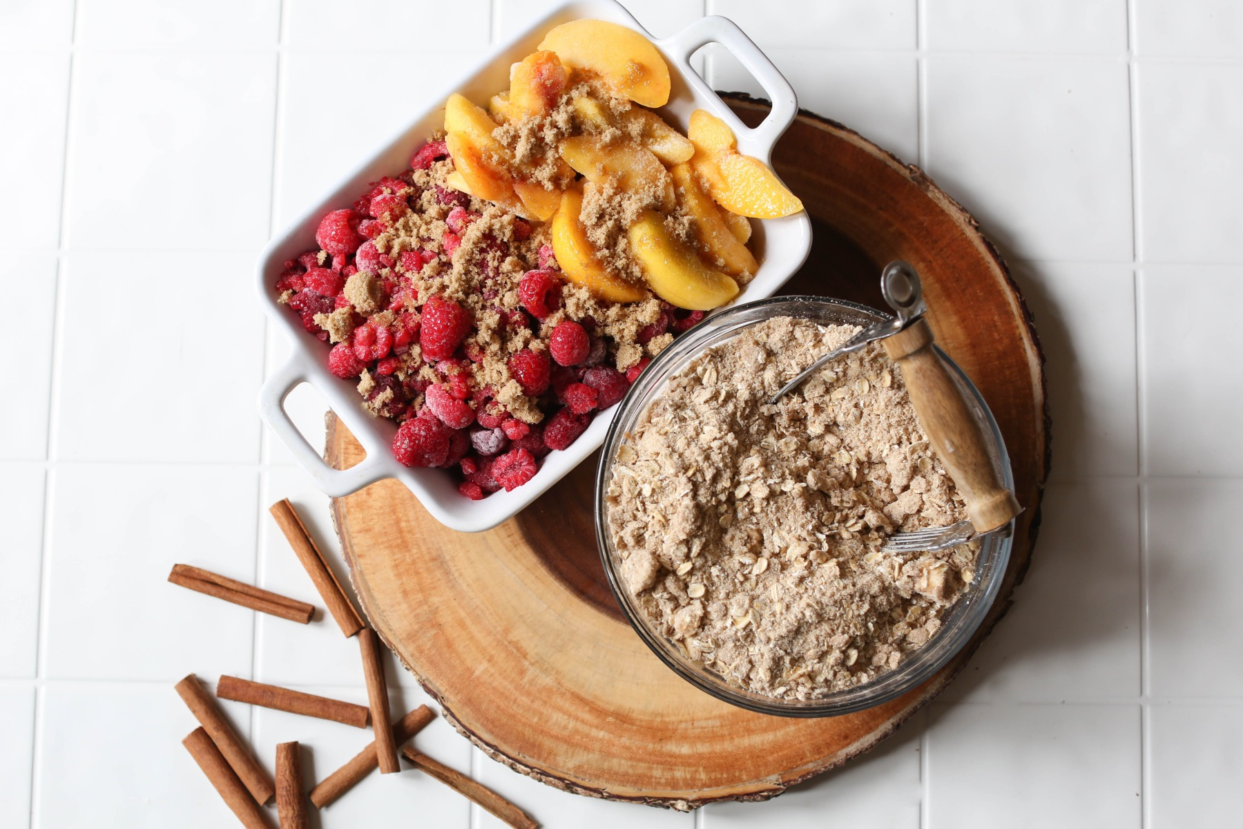 top the peach crisp crumble on the peaches and raspberries