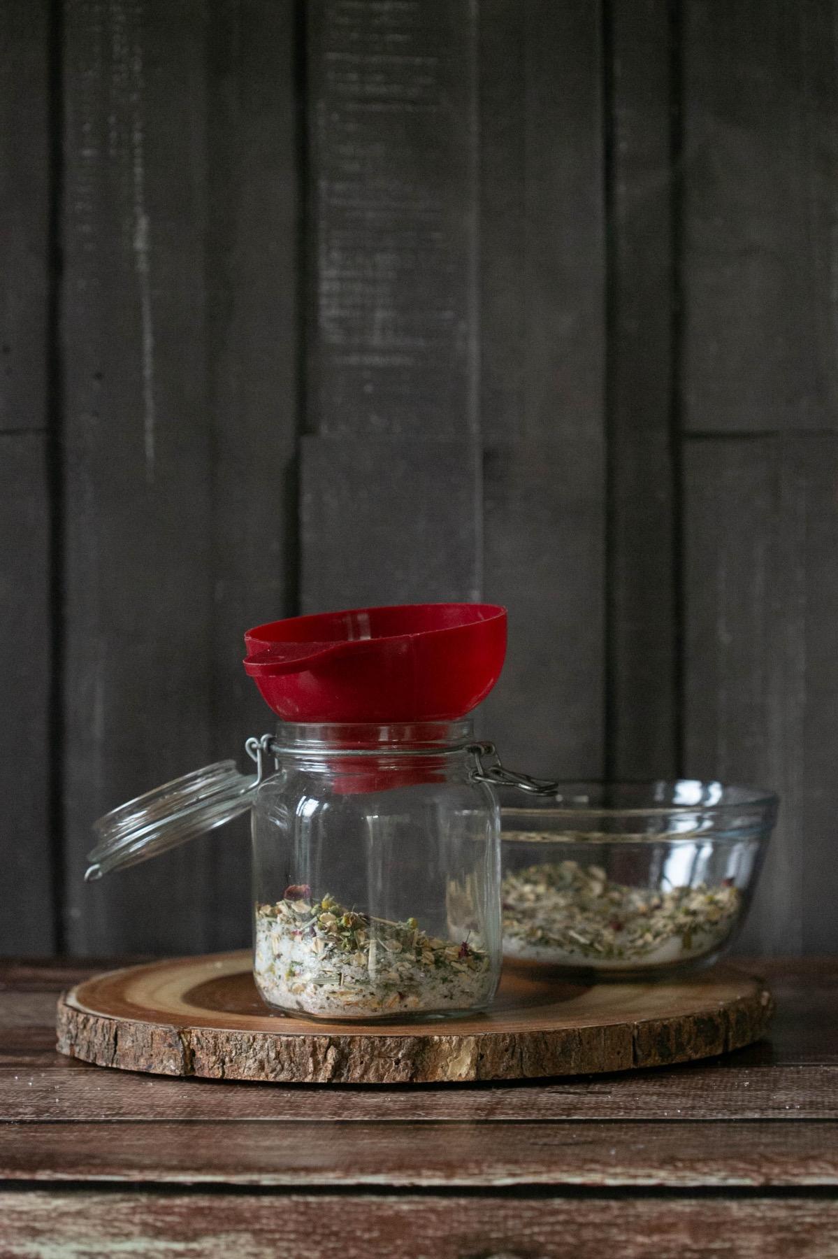 adding the relaxing bath soak recipe to a jar
