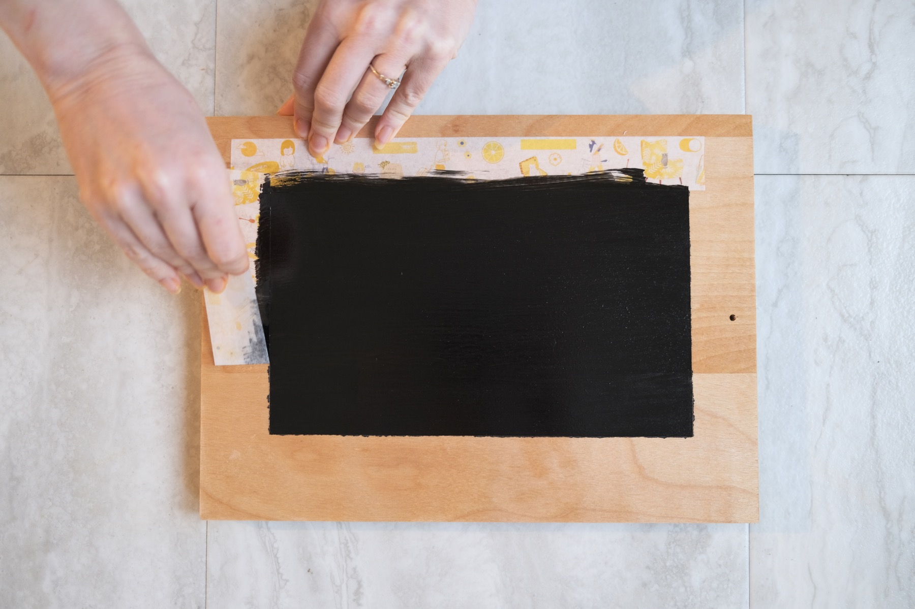 removing washi tape to reveal chalkboard painted tray