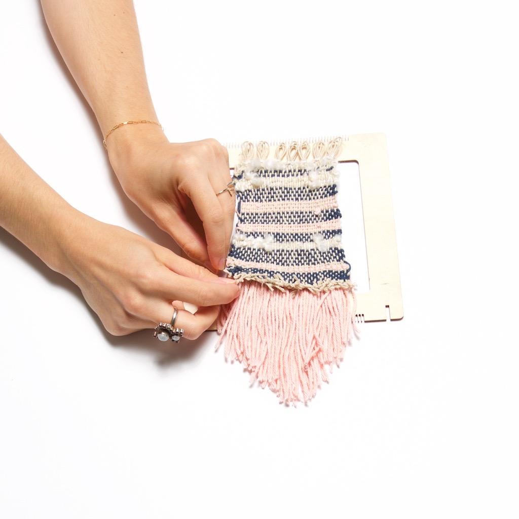 tuck the ends to finish a diy weaving wall hanging