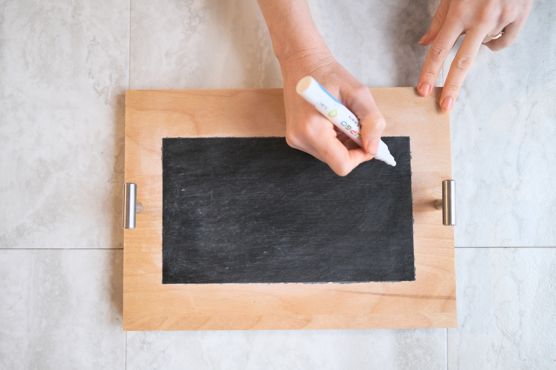 use a chalk pen on the chalkboard serving tray