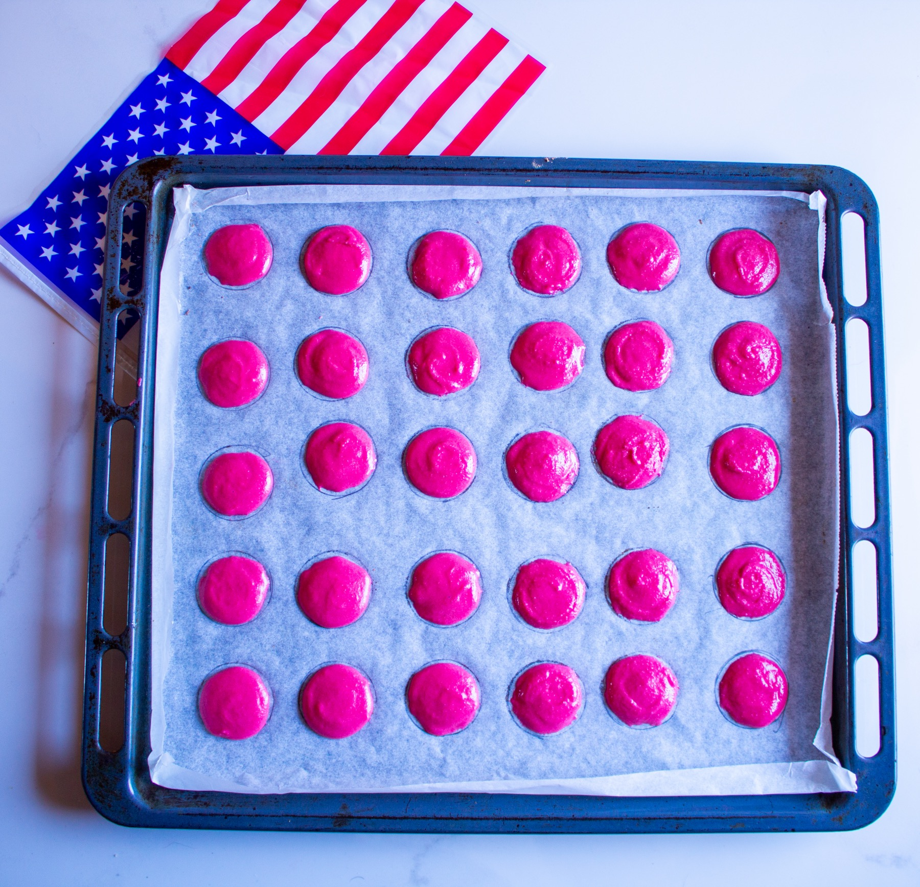 red macarons on a cookie sheet ready to bake