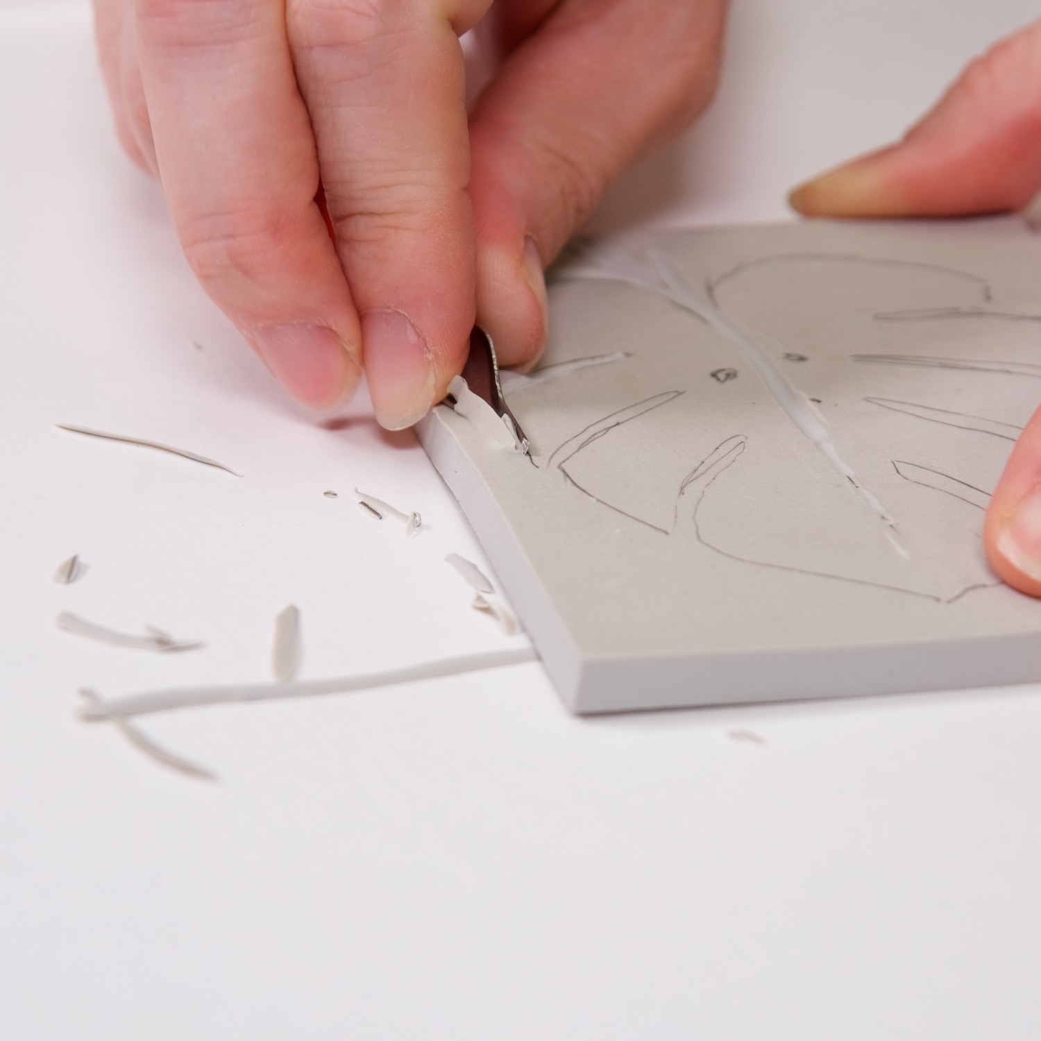 start by carving the edge of the linocut block