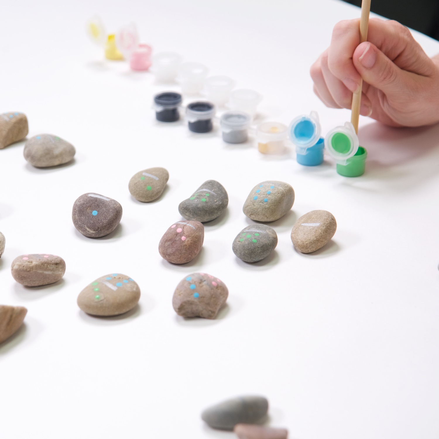 close up of painting the numbers on a diy rock domino set