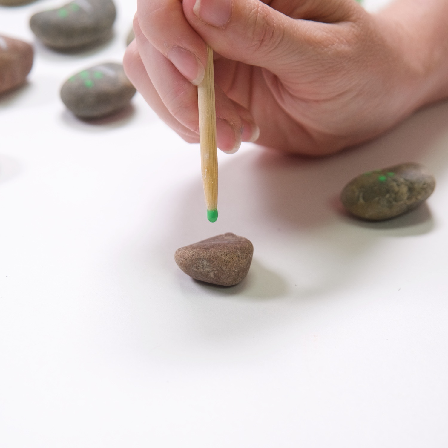 paint dots with a wood skewer to make rock dominoes