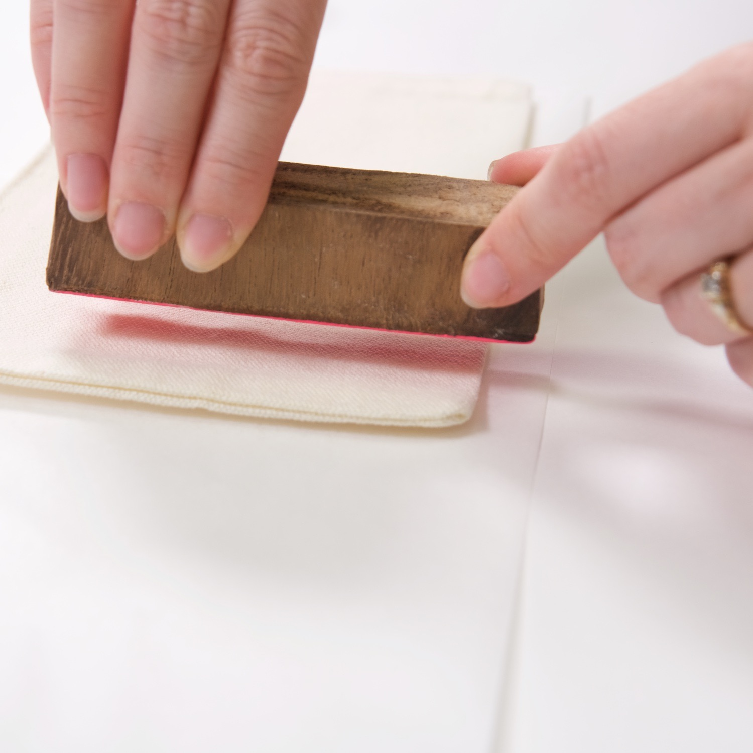 close up of pressing the wood block on the coin purse