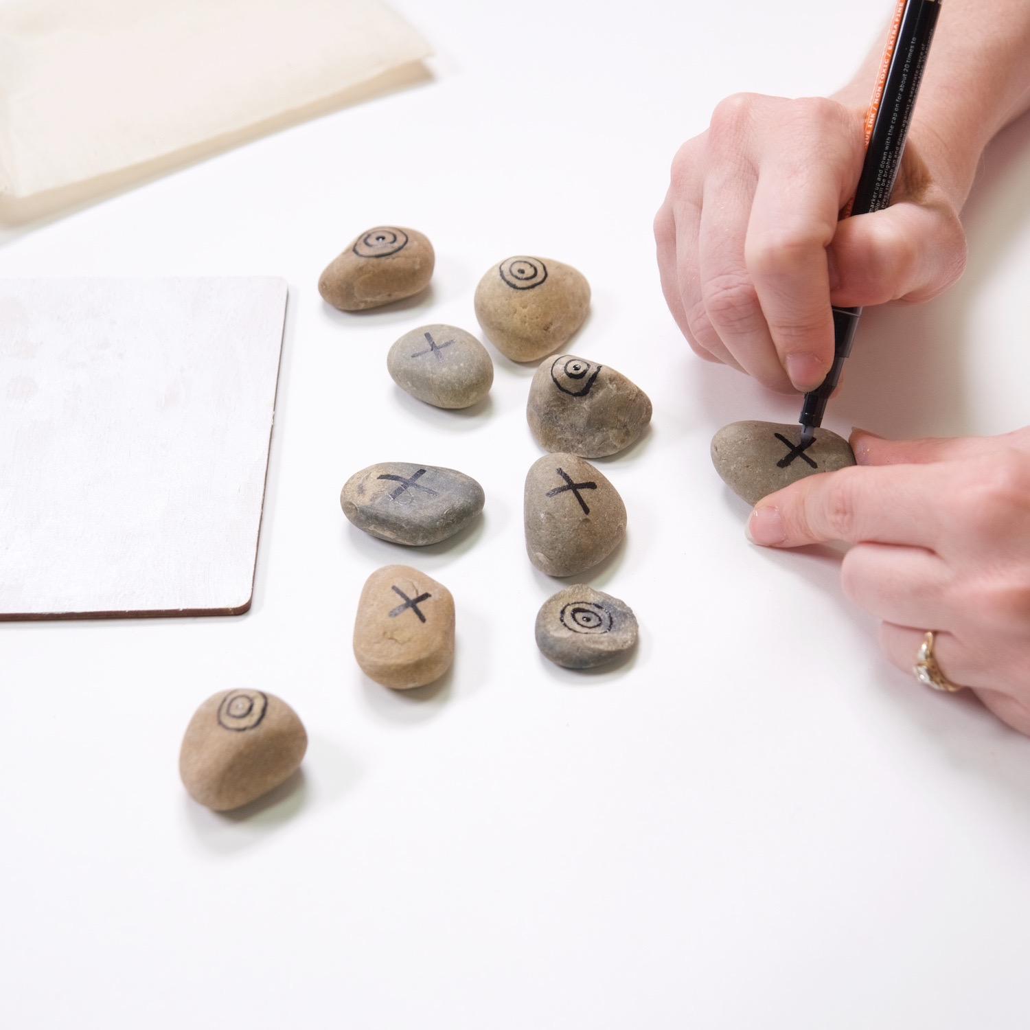 use a paint pen to make painted rock tic tac toe