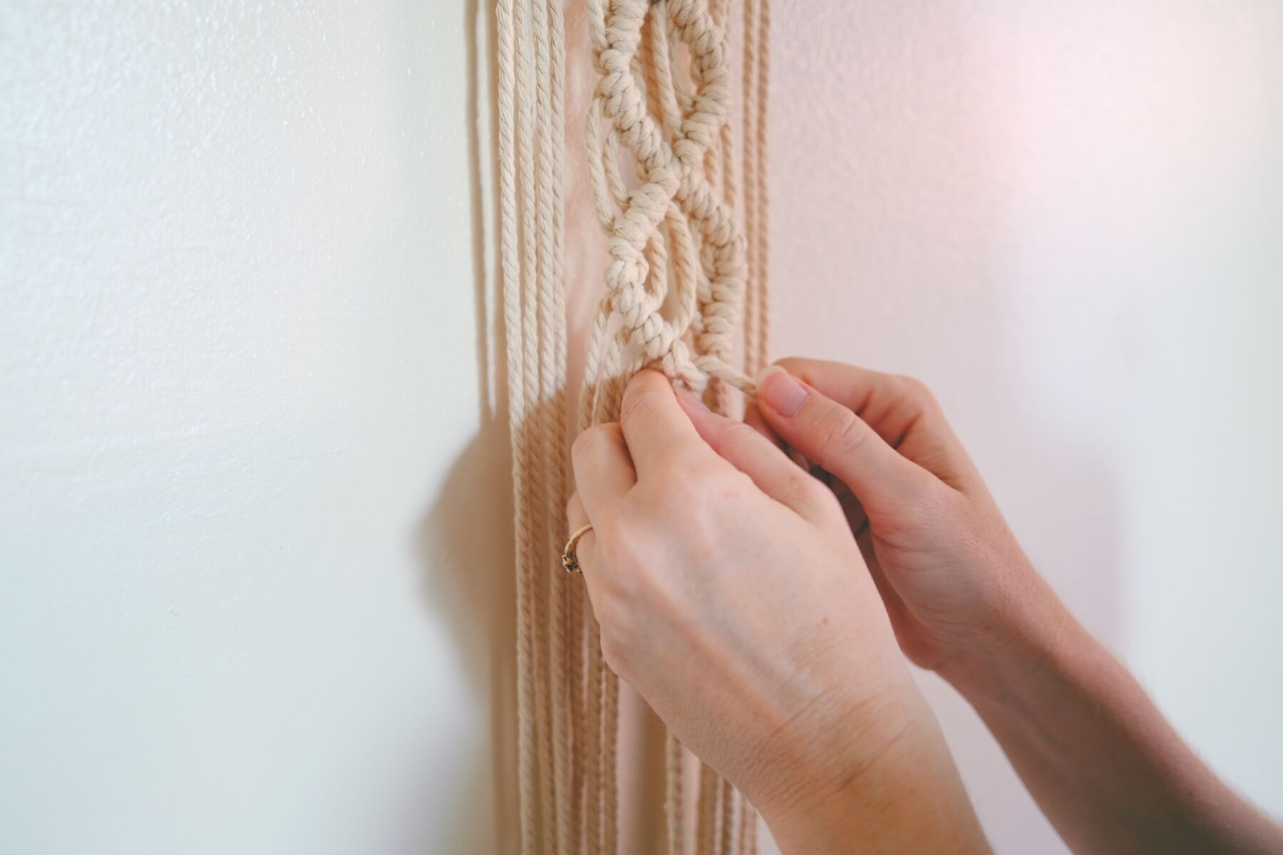 finishing the macrame knot work on the wall hanging